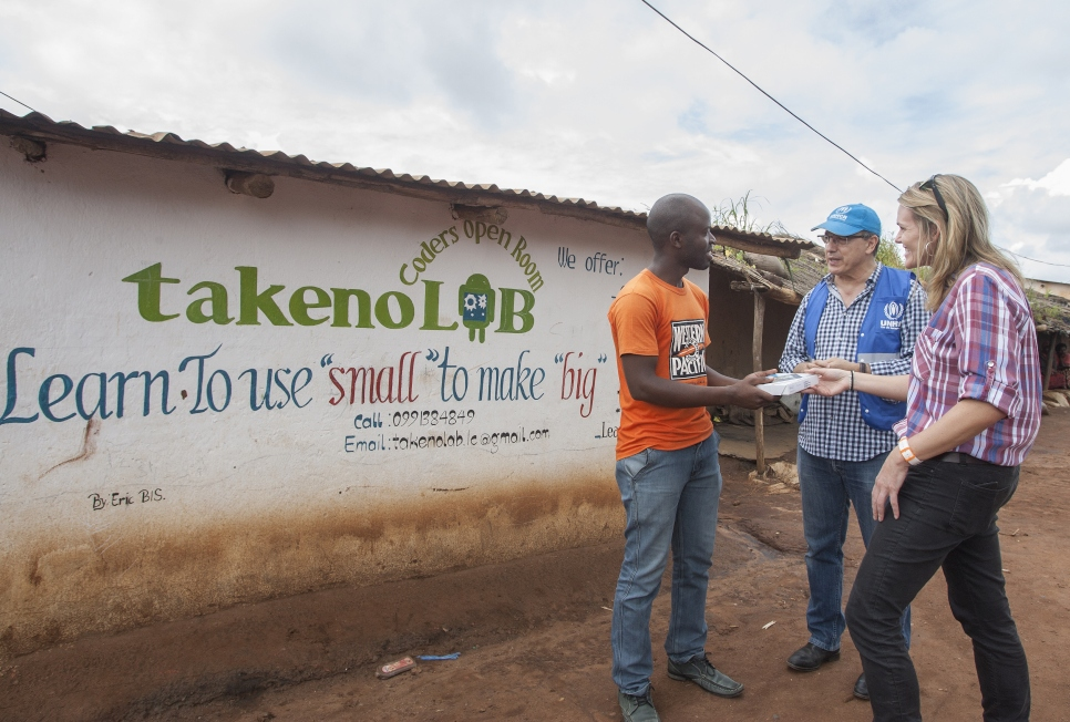 Remy Gakwaya, a 22 year old Burundian refugee stands outside his takenoLab centre in Dzaleka Camp, where he teaches other refugee youth to programme and code. With him are Kate Krukiel, Director of Partnerships from Microsoft and Kamel Deriche, UNHCR. Gakwaya is one of the refugee ambassadors for the Microsoft Connectivity project.