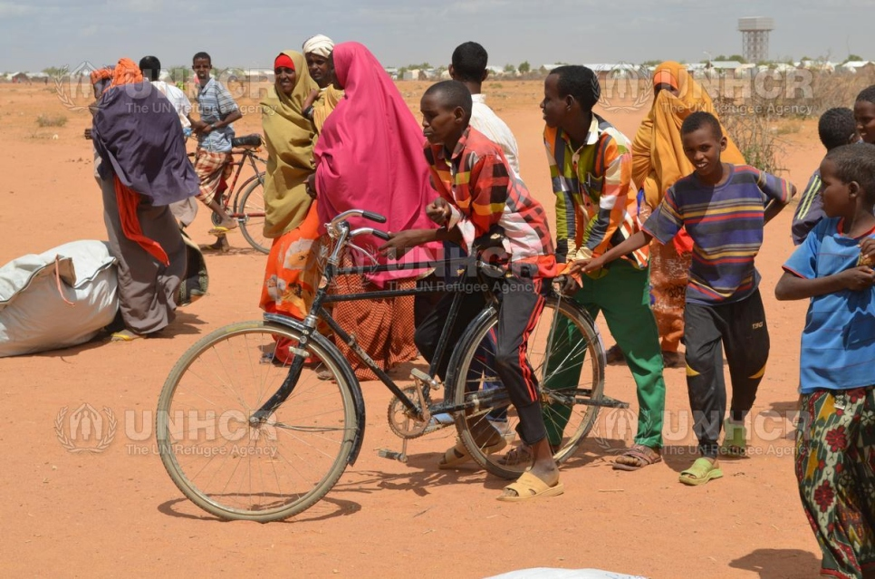 Kenya. Somali children share bicycle in Ifo 2 camp