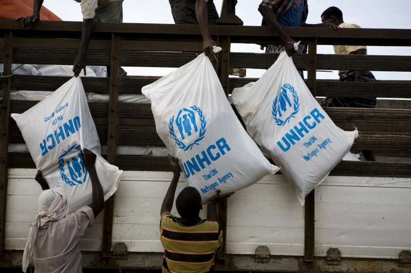 Aid items are unloaded from a truck at the Al Adala settlement, Somalia, 2011