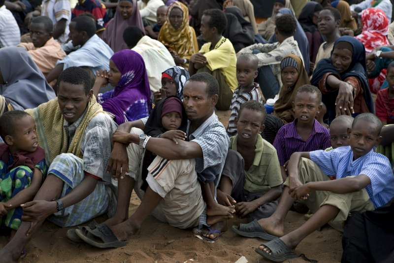 Refugees waiting to be registered sit in front of the UNHCR registration offices at Dadaab camp, 2010