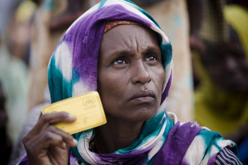 An internally displaced Somali woman, holding her registration card, waits for humanitarian supplies flown to Mogadishu