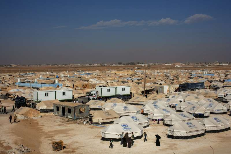 Trucks pull pre-fabricated homes through the centre of Zaatari camp. UNHCR relocated about 2,000 refugee families to these homes, which provide better protection and insulation in winter