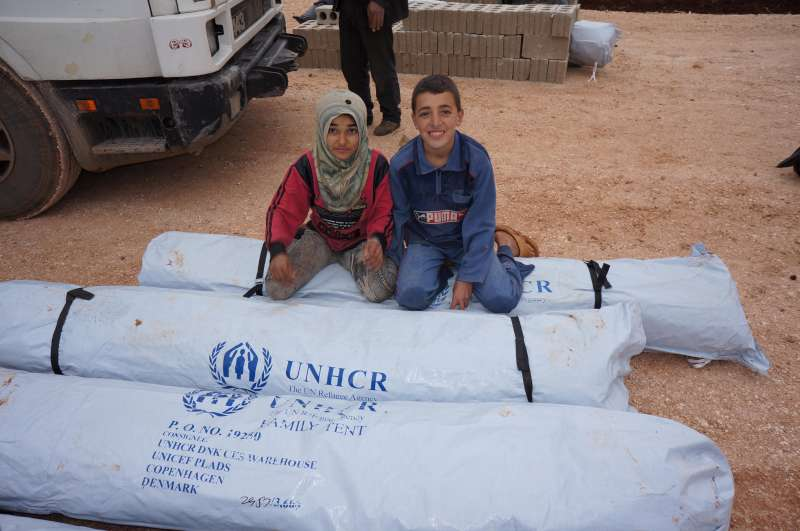 Displaced Syrian children sit on a UNHCR tent in Syria, February 2013
