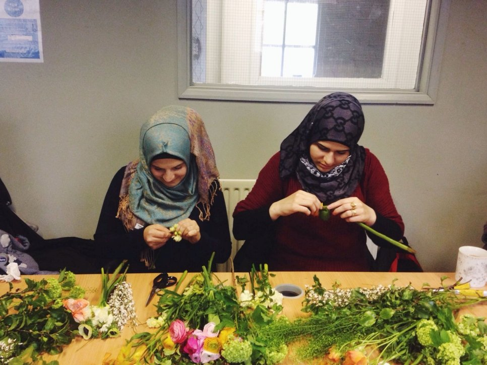 Women create flower arrangements together at a Bread and Roses workshop