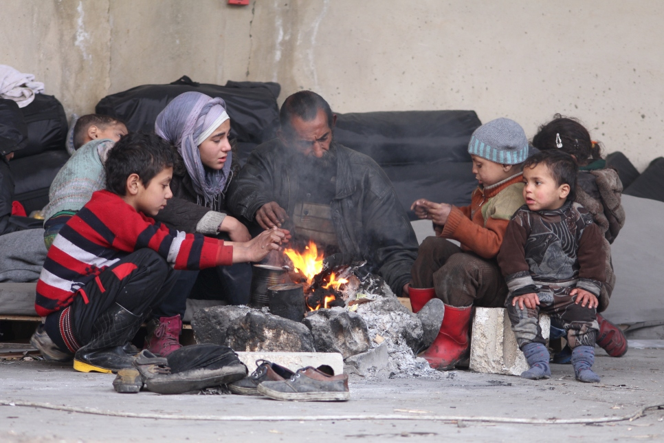A family displaced from their homes in east Aleppo try to keep themselves warm around a fire in the Jibreen industrial zone of the city, where warehouse buildings have been converted into temporary accommodation for thousands of people.