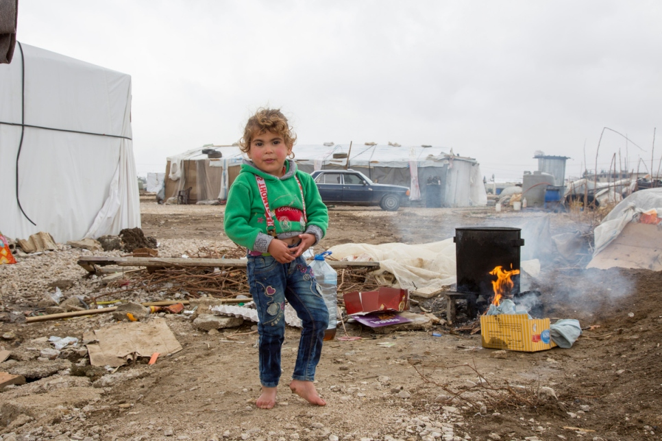 Lebanon. Syrian refugee girl stands barefoot in an informal settlement during winter