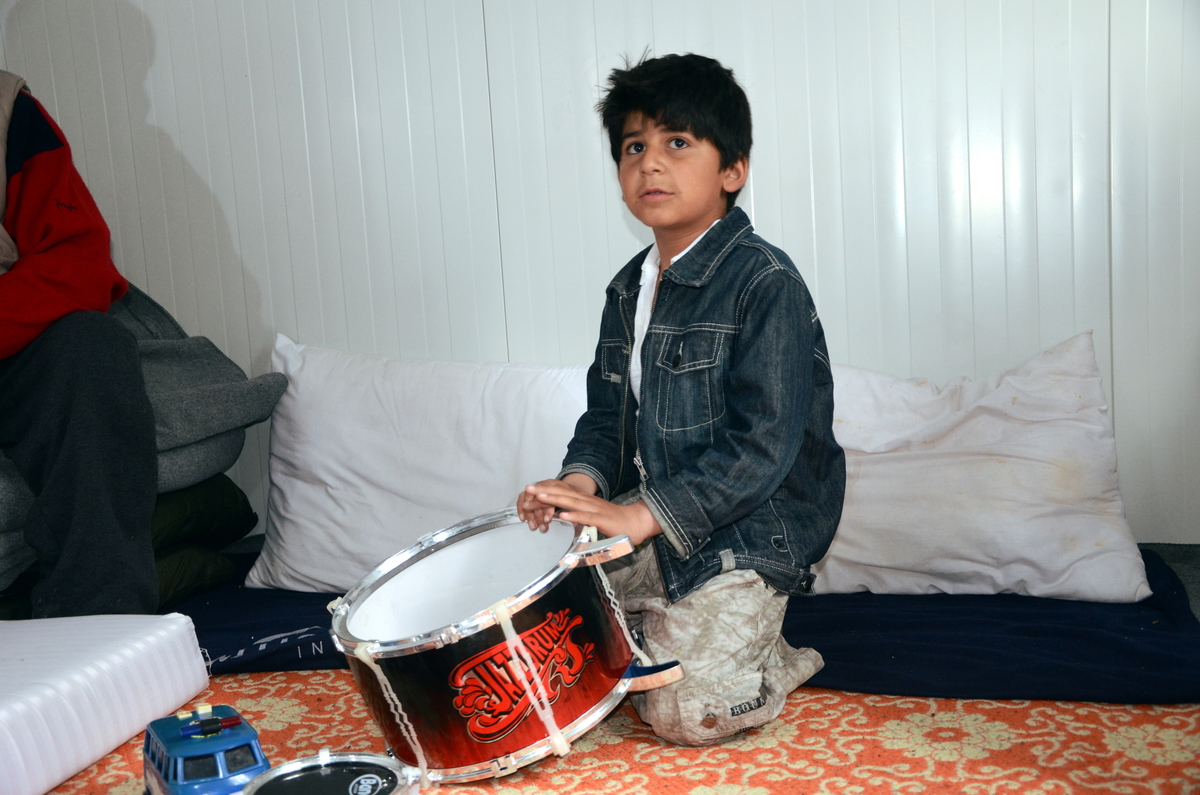 Afghan boy Farzad that stopped taliking after separation from his mother, playing on drums in a UNHCR prefab in Karatepe site
