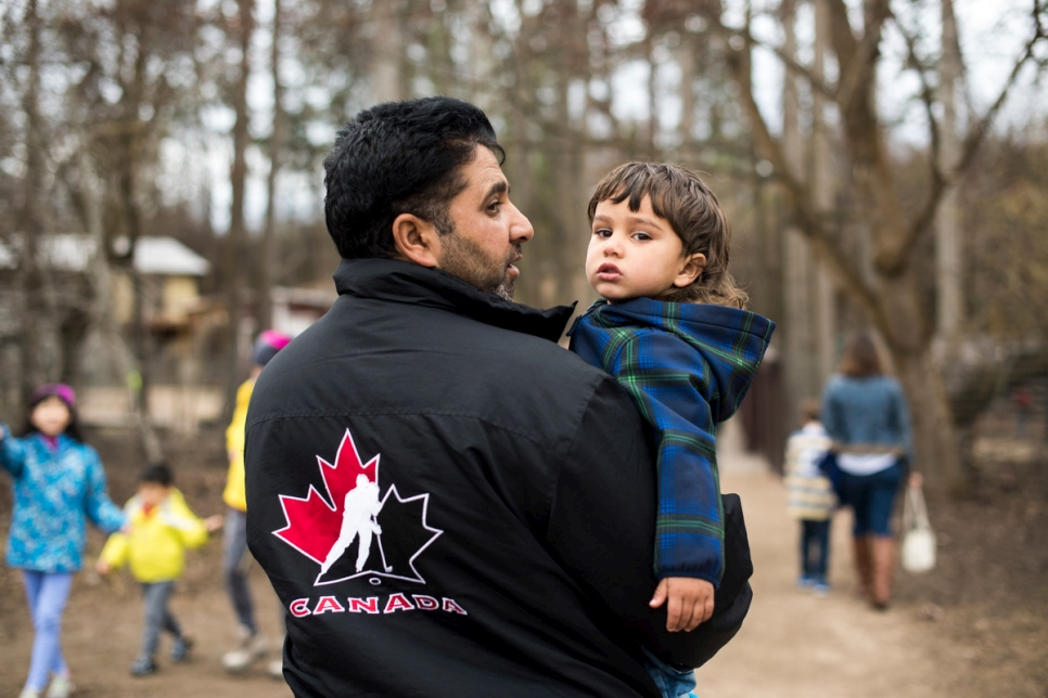 Canada. Mohammad, a Syrian refugee man carrying his youngest son at a petting zoo