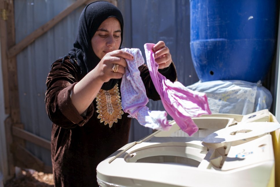 Jordan. A Syrian refugee, Asmahan, uses a washing machine in Azraq refugee camp