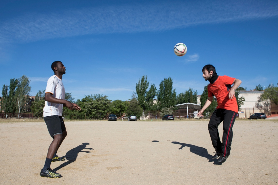 Asylum-seeker Ismael plays football with his Spanish mentor Javier.
