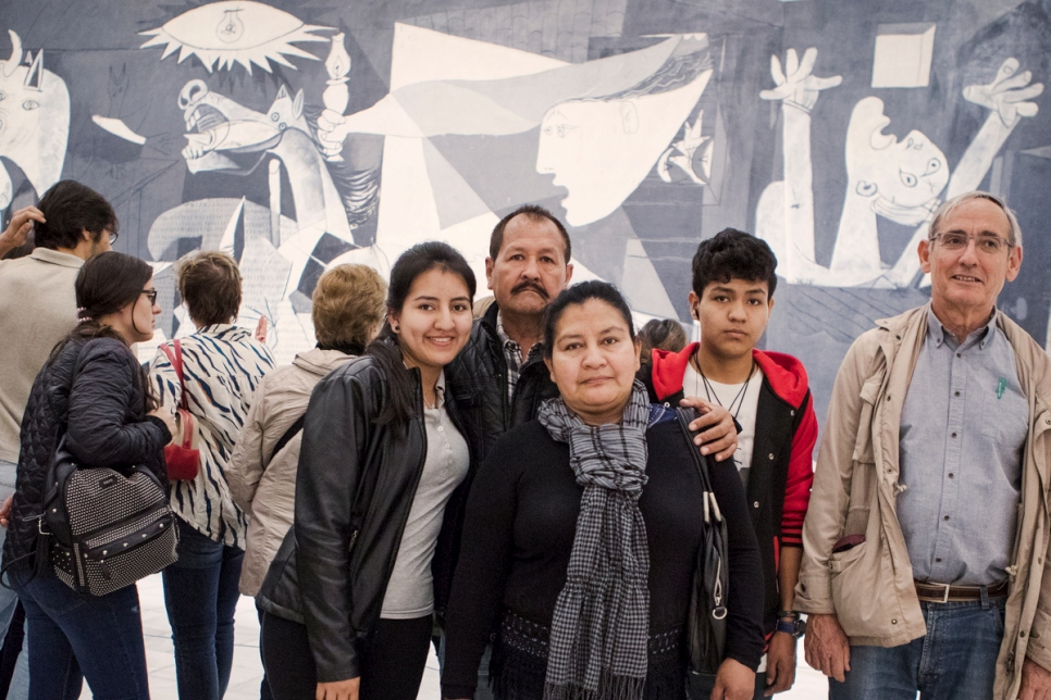 Spanish mentor Jose Maria Zamarrón (R) with the Colombian refugee family he mentors, Jose Ricaute, his wife Nelly and two of their children, in front of Picasso's Guernica.