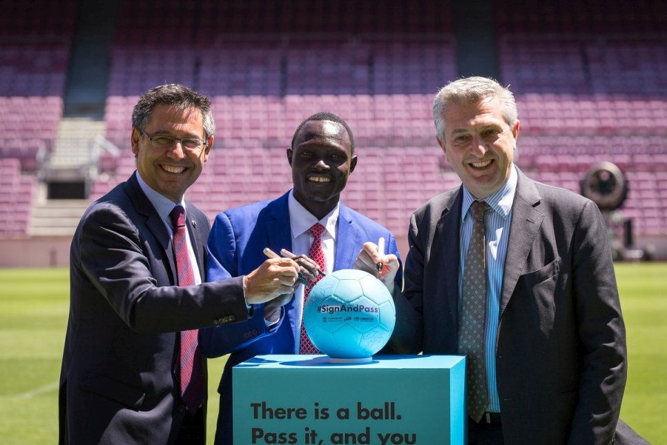 Spain. Josep Maria Bartomeu, Paulo Lokoro and Filippo Grandi sign off the ball of the \X6ESignAndPass campaign in the Camp Nou footbal field.