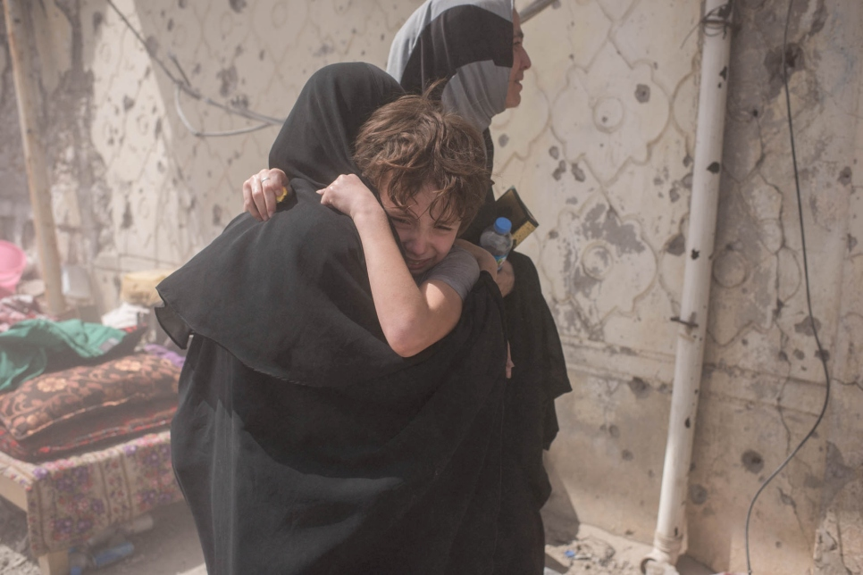 A mother and son embrace after being separated while fleeing fighting in the Old City of Mosul on June 24, 2017.