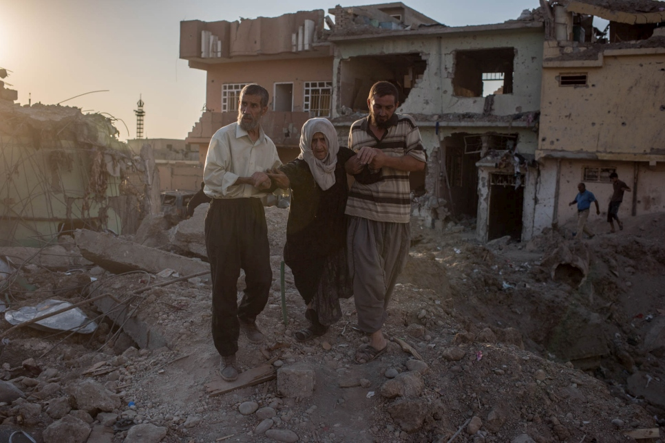 Two men help an elderly woman flee Mosul, Iraq on June 24, 2017.
