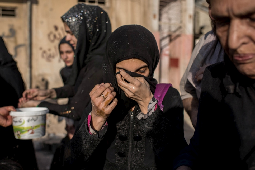 An Iraqi girl cleanses her face with water after reaching Iraqi government controlled area of Mosul, Iraq on June 23, 2017.
