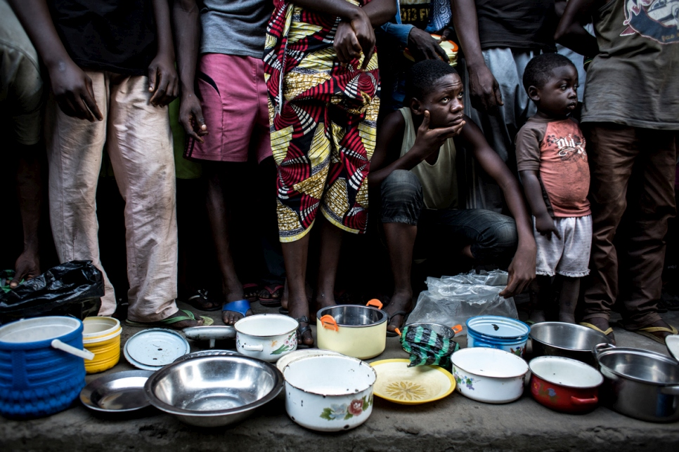 Internally displaced Congolese families from Kasai province wait in line for food in the grounds of a former clinic in the town of Idiofa, Democratic Republic of the Congo.
