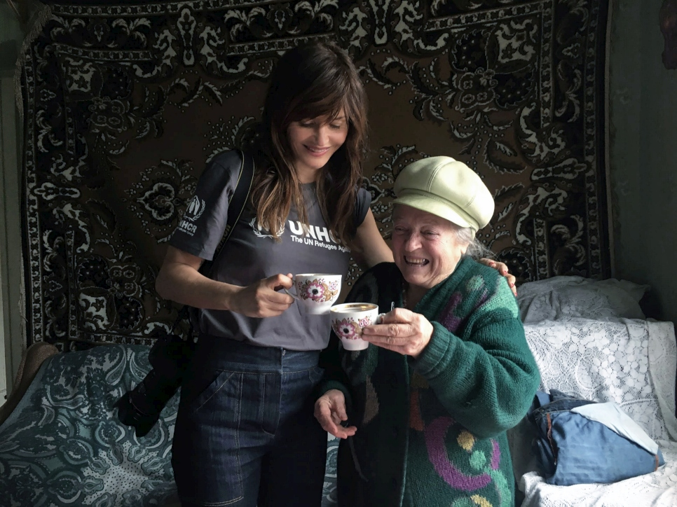 Helena shares a cup of fruit tea with Vera in her recently repaired home.