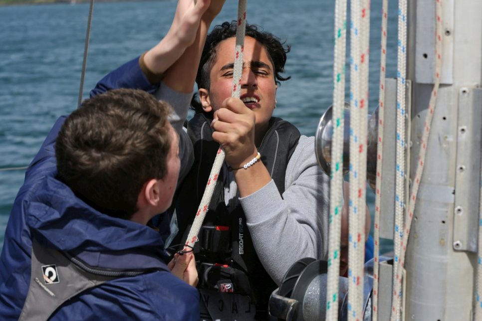 Adnan, an asylum-seeker from Syria, and Diarmaid from Ireland raise the sail.