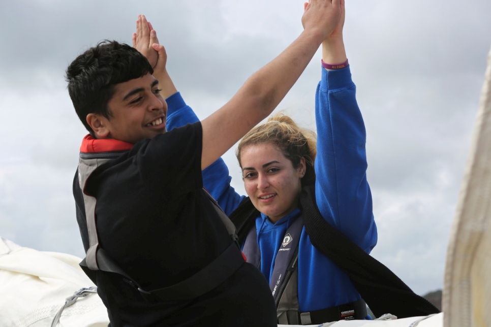Caylan from Ireland and Omran from Syria learn how to sail together.
