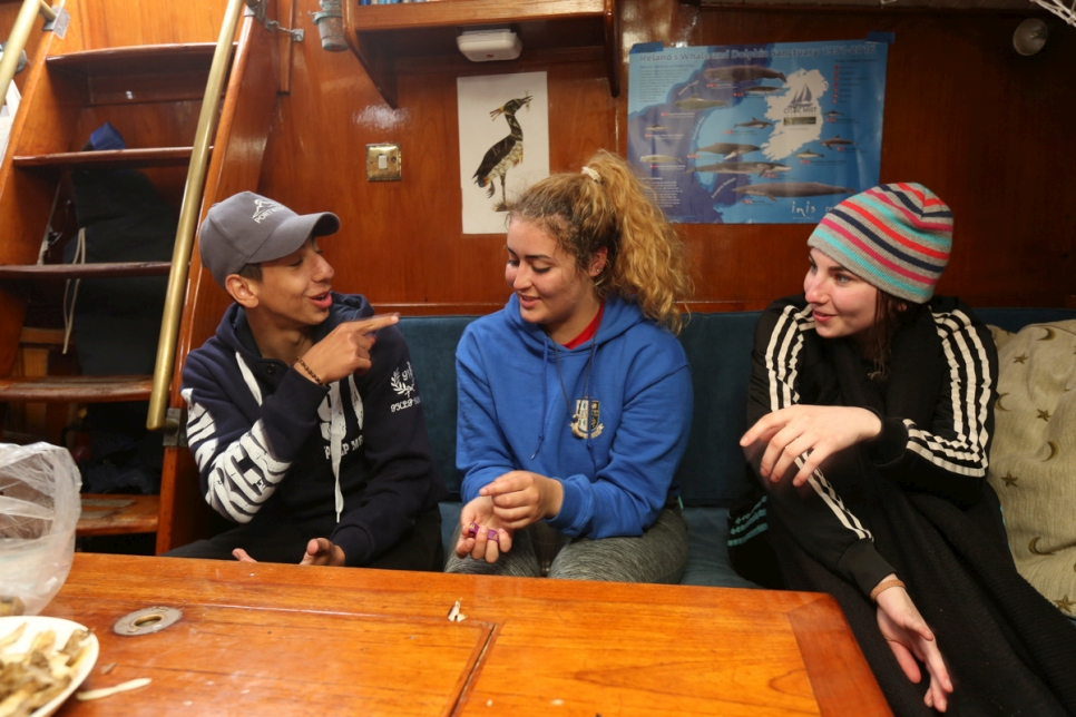 Teenagers chat below deck on board the spirit of Oysterhaven yacht.