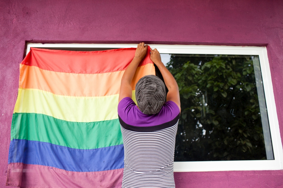 A person hangs a rainbow flag to a window.