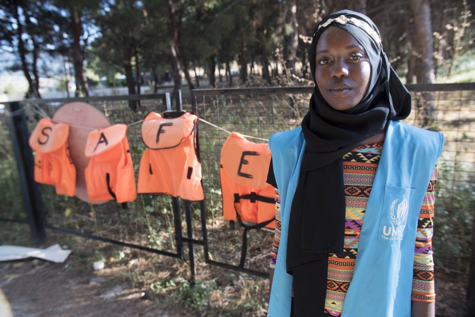 Emi stands in front of a selection of lifejackets. Many now line the beaches of Lesvos.