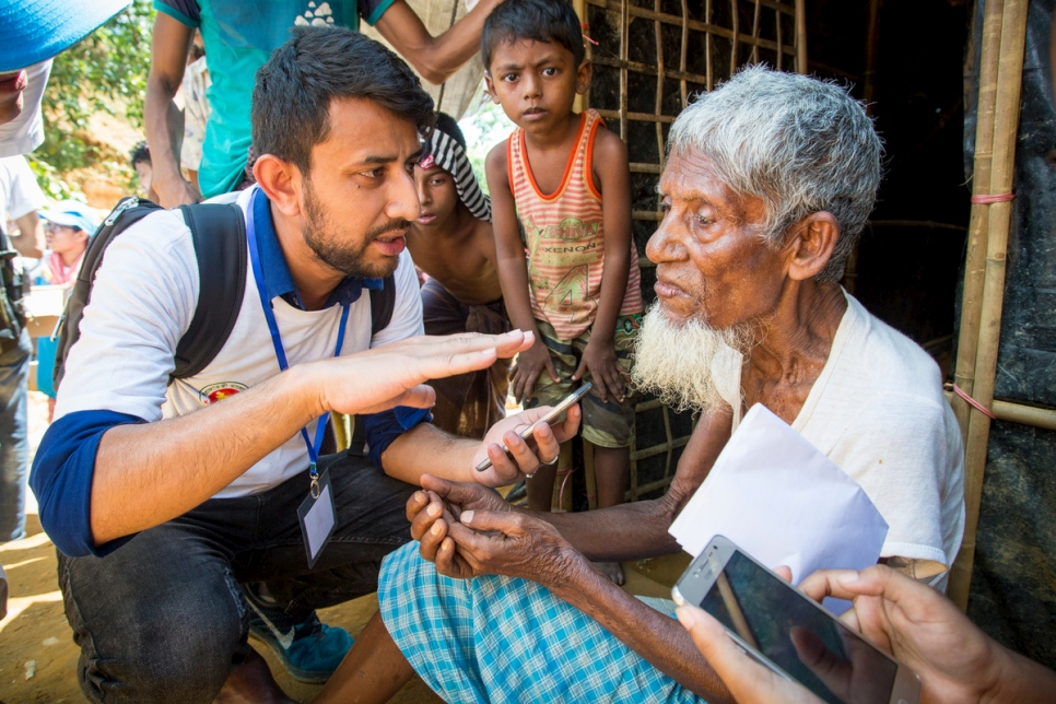 A UNHCR contractor collects information from Mohammad Busho, 80, using a data-gathering smartphone app that helps to streamline assistance at the Kutupalong extension site, Bangladesh