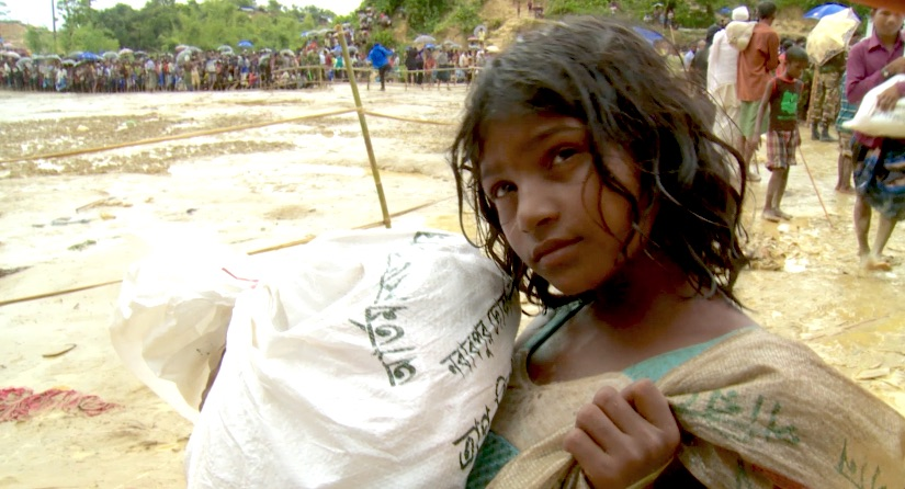 Rohingya girl carries donated aid