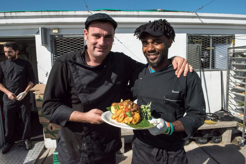 Eze (right) presents jollof rice with fried plantain, alongside head chef Adrian.
