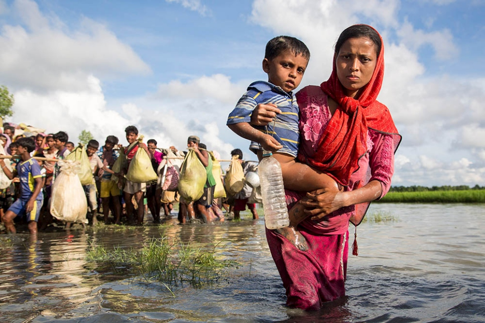 A Rohingya mother wades through water as she crosses the border from Myanmar into Bangladesh, near the village of Anzuman Para in Palong Khali.