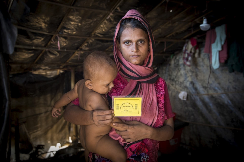 A Rohingya mother holds up the card given to her by UNHCR volunteers collecting information using a data-gathering smartphone app at the Kutupalong extension site.