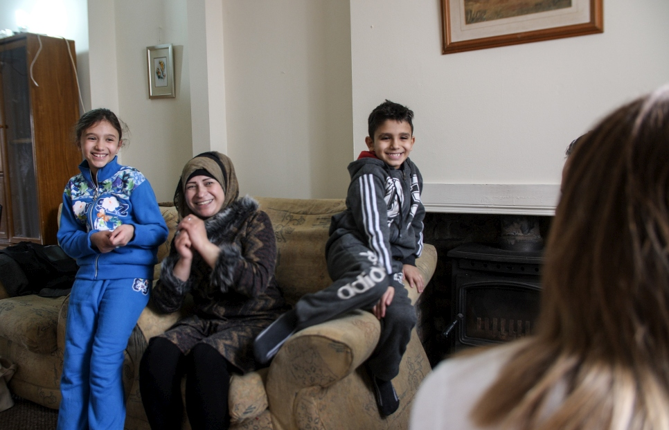 A Syrian family, Maisaa and her two children Esraa and Yahya, speak to their key worker Catherine at their new home in Armagh, Northern Ireland.