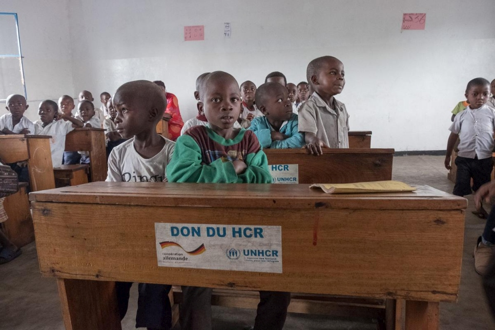 Formerly displaced children sit in a new classroom constructed and equipped by UNHCR in Rusayo, DRC.  The extension of the school has helped increase the number of students from 400 to almost 600.