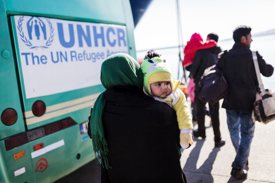A woman carrying her young child walks towards a UNHCR bus that will transport them to the Moria Reception / Registration center where they will register with Greek Authorities before continuing their journey towards Athens.