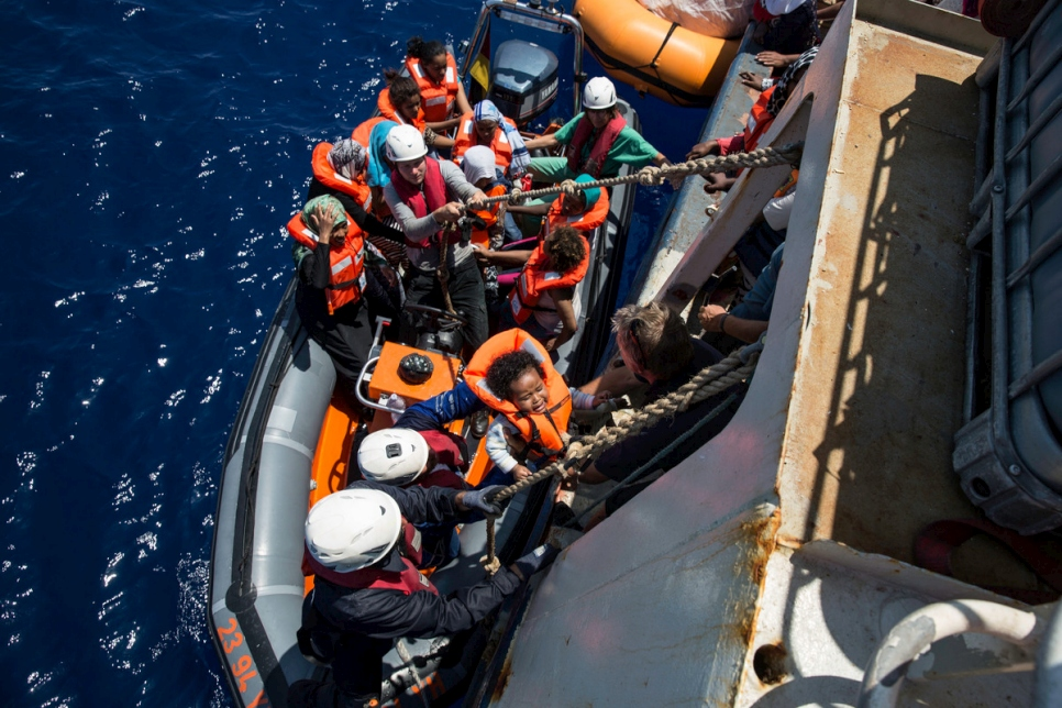 Crew from a Sea Watch search and rescue vessel rescue survivors from a boat that foundered trying to cross the Mediterranean to Europe from Libya in 2016.