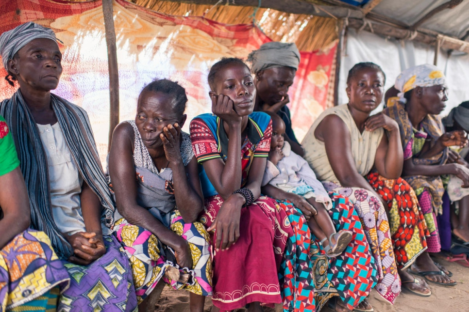 Several colourfully dressed Congolese women sit in a row, lamenting the kidnapping of their children.