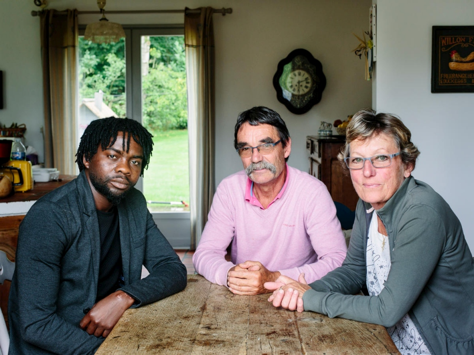 France. Catherine and Jean-Pierre host Assadik, a refugee from Sudan, in Saint-Josse. This portrait is part of the No Stranger Place series, which portrays locals and refugees living together