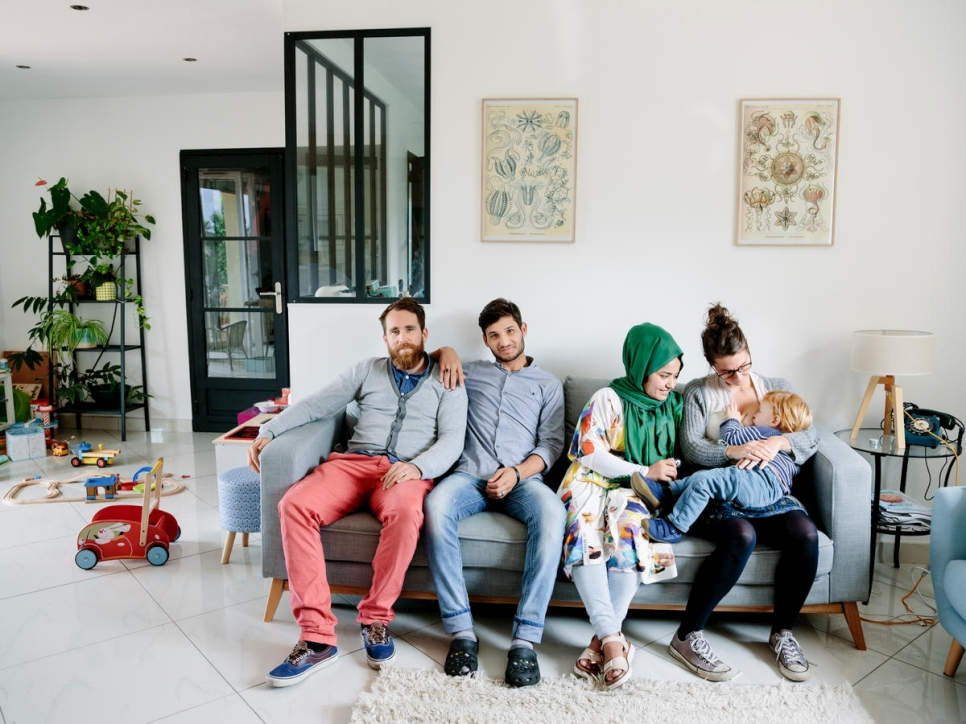 France. Anaïs, Vincent, and their son César, host Afghan refugees Zulfeqar and Battarine, in Saint-Priest. This portrait is part of the No Stranger Place series, which portrays locals and refugees living together