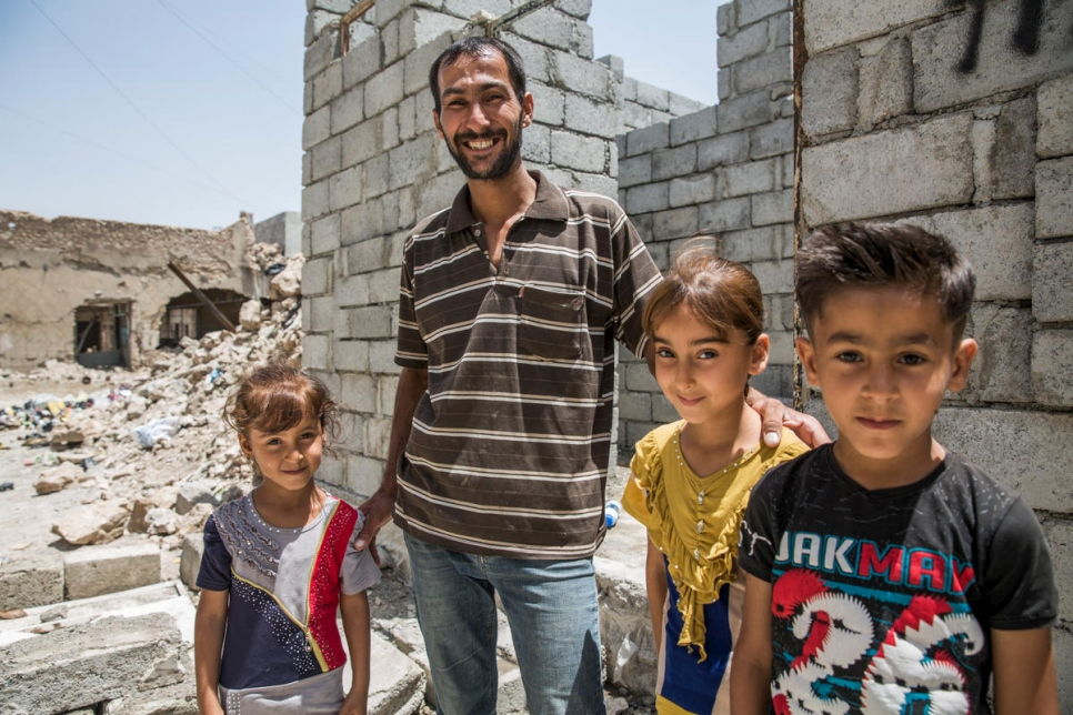 A displaced Iraqi father stands with his three children outside the new home he is building in West Mosul, Iraq.