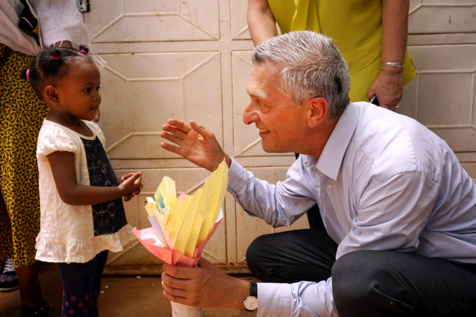 UN High Commissioner for Refugees Filippo Grandi (right) crouches to speak with a young refugee girl.