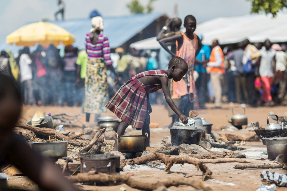 Uganda. A young South Sudanese refugee cooks food at a camp in northern Uganda