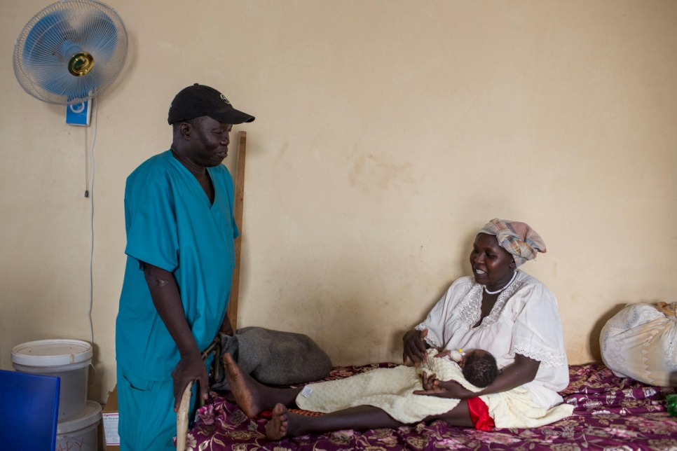Dr. Evan Atar Adaha talks to a patient from Sudan, Gisma Al Amin, in the maternity ward of Bunj Hospital in Maban County, South Sudan.
