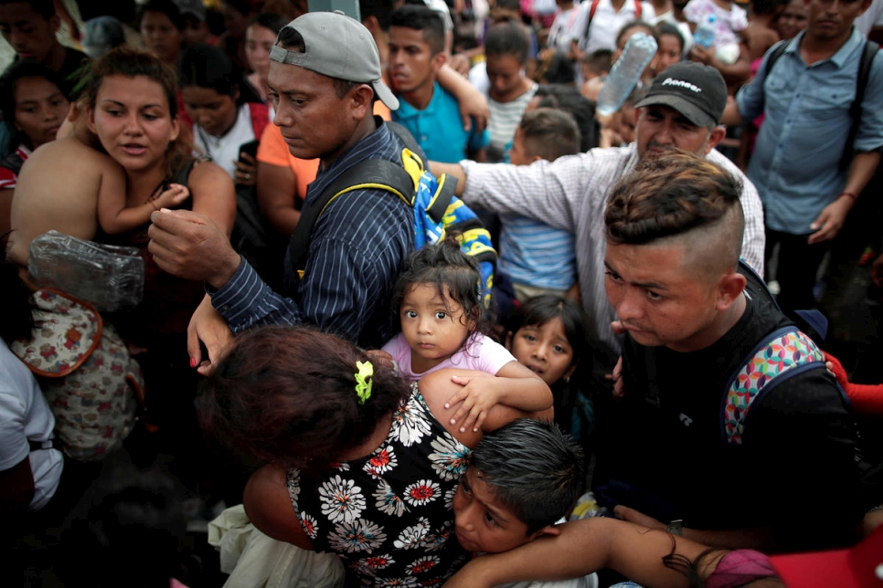 Children of Central American migrants wait with their parents to apply for asylum in Mexico at a checkpoint in Ciudad Hidalgo