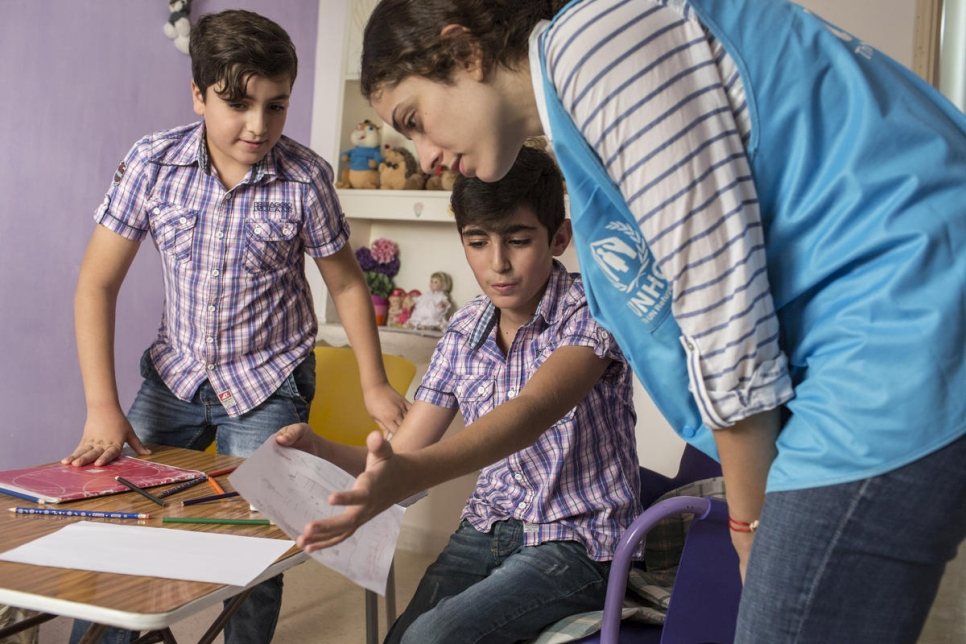 Syrian refugee children, Adib (left), 9, and his brother Khaled, 10, draw a picture of their memories of the war in Syria, with a UNHCR worker at their home in Damour, Lebanon.