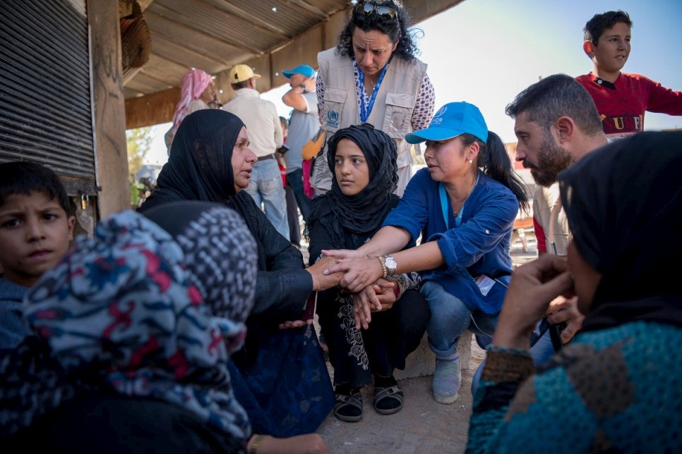A UNHCR staff comforts a mother in Rasem Alharmal, a small village in rural Aleppo with a pre-crisis population of 1,500 people. Around 1,000 have returned since fighting ended in April 2017. Most found their houses destroyed and looted.