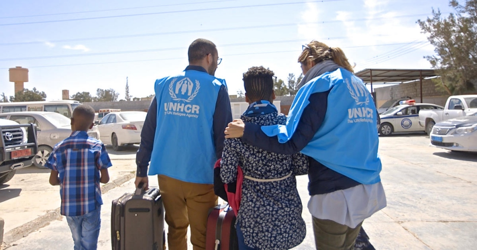 Libya. UNHCR staff members accompany 2 Eritrean kids out of a Libyan detention center