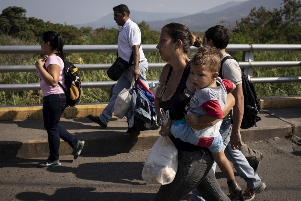 A Venezuelan mother holds her child as she crosses the Simon Bolivar Bridge to Colombia, in  January 2019.