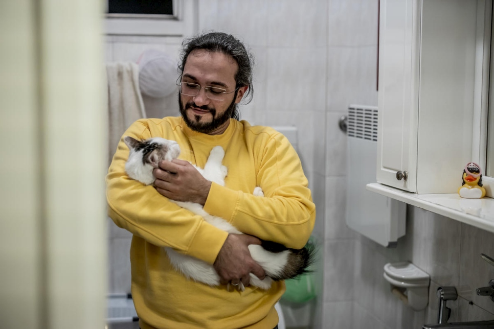 At home in Belgrade, Mawaheb cuddles his cat, Fidel. They have been together since shortly after Mawaheb fled the war in Syria.