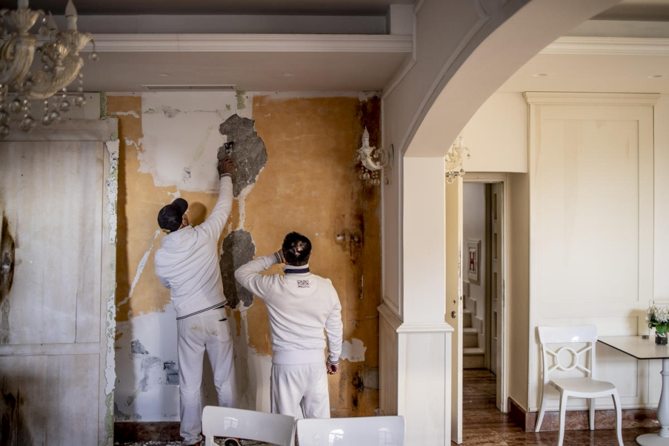 Roberto (left) and Silvio plaster a wall at the Villa Perast Hotel.