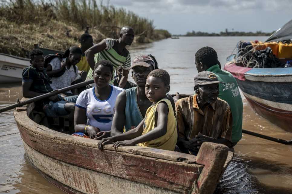 A small boat pulls into the  Buzi dock carrying residents. Many people displaced from Buzi in the aftermath of Cyclone Idai are returning to check on the status of their homes and belongings.